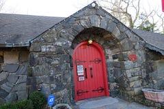 A puerta cerrada rojo en un edificio fuerte construido con la pared de piedra fuerte imágenes de archivo libres de regalías