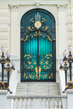 Puerta clásica de acero del negro y del oro en el estilo de Europa con el edificio blanco Imagen de archivo