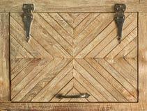 Puerta con bisagras de madera con ángulos decorativos y una manija foto de archivo