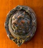 Puerta con el golpeador de cobre amarillo en la forma de un león, entra hermoso Fotografía de archivo