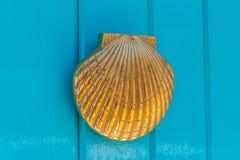 Puerta con el golpeador de cobre amarillo en la forma de una cáscara, entr hermoso Imágenes de archivo libres de regalías