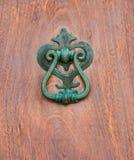 Puerta con el golpeador de cobre amarillo en la forma de una decoración, entr hermoso Foto de archivo libre de regalías