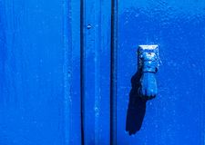 Puerta con el golpeador de cobre amarillo en la forma de una mano, entra hermoso Fotografía de archivo libre de regalías