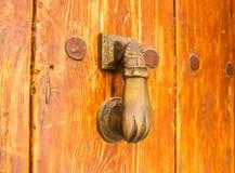 Puerta con el golpeador de cobre amarillo en la forma de una mano, entra hermoso Fotografía de archivo