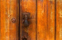 Puerta con el golpeador de cobre amarillo en la forma de una mano, entra hermoso Imágenes de archivo libres de regalías