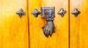Puerta con el golpeador de cobre amarillo en la forma de una mano, entra hermoso Fotos de archivo libres de regalías
