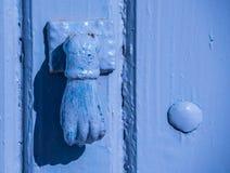 Puerta con el golpeador de cobre amarillo en la forma de una mano, entra hermoso Foto de archivo libre de regalías