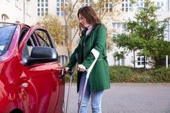 Puerta de abertura de la mujer discapacitada de un coche imagenes de archivo
