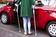 Puerta de abertura de la mujer discapacitada de un coche imagen de archivo
