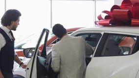 Puerta de abertura profesional del vendedor de coches de un coche para su cliente masculino almacen de metraje de vídeo