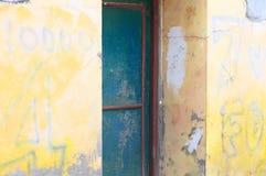 Puerta de acero azul y un fondo amarillo de la pared fotos de archivo