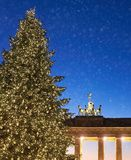Puerta de Brandeburgo en Berlín con el árbol de navidad y la nieve que cae Fotos de archivo