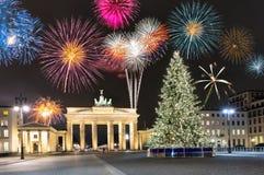 Puerta de Brandeburgo en Berlín, con los fuegos artificiales y el árbol de navidad Imagenes de archivo