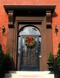 Puerta de Brown con la guirnalda de la Navidad Imágenes de archivo libres de regalías