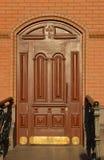 Puerta de caoba de madera en una pared de ladrillo Imágenes de archivo libres de regalías