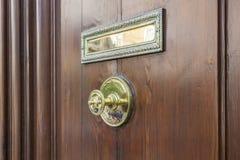 Puerta de entrada de madera con la manija de oro Foto de archivo libre de regalías