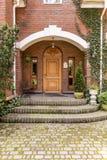 Puerta de entrada elegante, de madera a un estado con la hiedra que crece en b imagenes de archivo