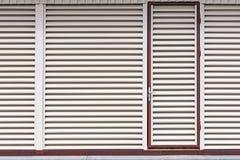 Puerta de entrada en el edificio del almacén lumbrera de la hoja de metal con las barras horizontales imagen de archivo