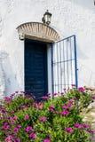 Puerta de entrada vieja azul española con la puerta abierta en la casa blanca Foto de archivo