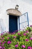 Puerta de entrada vieja azul española con la puerta abierta en la casa blanca Foto de archivo libre de regalías