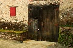 Puerta de granero vieja y ventana Shuttered rojo Fotos de archivo