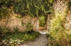 Puerta de la arcada y pared de piedra histórica en el escondrijo del jardín Fotografía de archivo