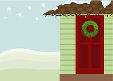 Puerta de la casa del invierno con la guirnalda Fotos de archivo libres de regalías
