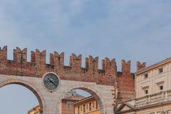 Puerta de la ciudad antigua con el reloj de Verona, Italia foto de archivo