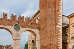 Puerta de la ciudad antigua con el reloj de Verona, Italia foto de archivo libre de regalías