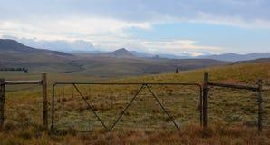 Puerta de la granja que lleva a las montañas Imagen de archivo libre de regalías