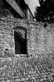 Puerta de la parrilla del hierro en la pared de piedra Foto de archivo