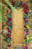 Puerta de madera adornada con las flores Foto de archivo libre de regalías