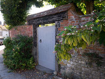 Puerta de madera al jardín en pueblo antiguo con las flores Fotos de archivo