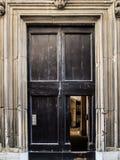 Puerta de madera antigua del roble con el portal de mármol del marco en la pared de ladrillo vieja, Urbino, Italia Foto de archivo