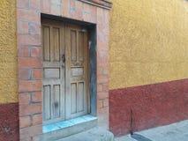 Puerta de madera antigua Mano-tallada rústica en pared mexicana texturizada primitivo del ladrillo y del estuco con el oro, moho, foto de archivo