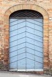 Puerta de madera azul con el arco en pared de piedra vieja Imagen de archivo