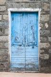 Puerta de madera azul vieja en pared de piedra rural gris Foto de archivo libre de regalías