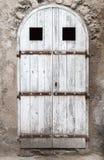Puerta de madera blanca vieja con el arco en la pared de piedra imagen de archivo libre de regalías