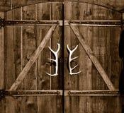 Puerta de madera con las manetas de la cornamenta fotografía de archivo