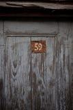 Puerta de madera con número rojo del metal Foto de archivo libre de regalías