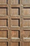 Puerta de madera de Brown con los remaches viejos del metal - los tonos retros texturizaron el fondo Imagenes de archivo
