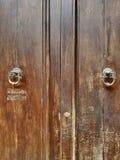 Puerta de madera de Brown con tirones de la puerta envejecido Ala doble sólido Imágenes de archivo libres de regalías