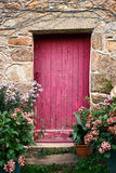 Puerta de madera de la pintura rosada brillante en casa de piedra vieja imagenes de archivo