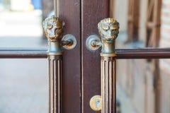 Puerta de madera del viejo estilo con las manijas bajo la forma de cabeza del ` s del león fotografía de archivo libre de regalías