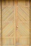Puerta de madera del vintage con los obturadores en una pared de ladrillo roja imagen de archivo