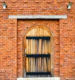 Puerta de madera en fondo rojo de la pared de ladrillo Fotos de archivo