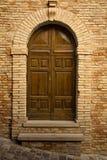 Puerta de madera en la arcada de piedra Foto de archivo