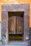 Puerta de madera estropeada mexicano del estilo del salón con la pared agrietada fotos de archivo