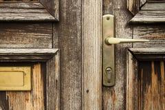 Puerta de madera gastada con la manija Foto de archivo
