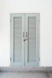 Puerta de madera gris cerrada y bloqueada, ventana bloqueada en la pared blanca b Imagen de archivo libre de regalías